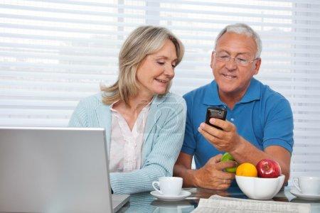 Photo pour Senior homme montrant téléphone portable à la femme - image libre de droit