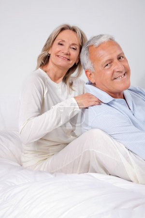 Photo for Portrait of happy couple sitting together on bed at home - Royalty Free Image