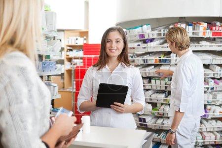 Photo pour Portrait de femme pharmacien détenant des tablet pc en client traitant sur le comptoir - image libre de droit