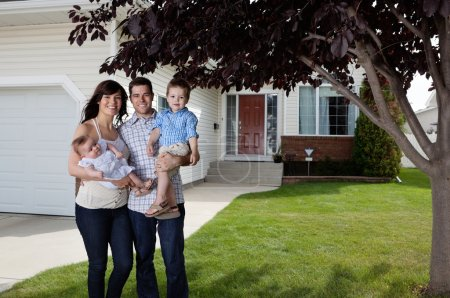 Photo for Portrait of happy couple standing with their children in front of house - Royalty Free Image