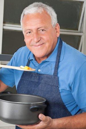 Photo pour Gros plan portrait d'un homme âgé dégustant de la nourriture - image libre de droit