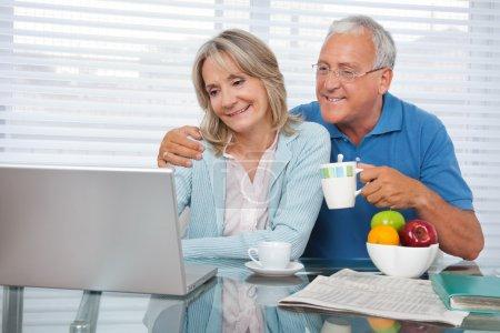 Photo pour Couple heureux en utilisant un ordinateur portable tout en prenant le petit déjeuner - image libre de droit