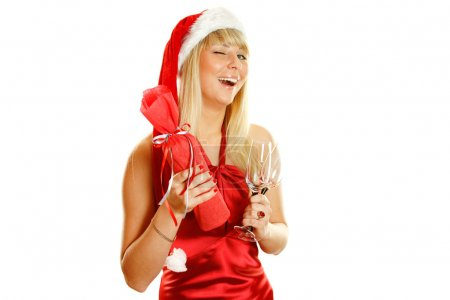 Photo pour Belle fille dans une robe rouge et un chapeau de Noël dans ses mains et deux verres de vin en boîte / bouteille de champagne. Des clins d'oeil. Isolé - image libre de droit