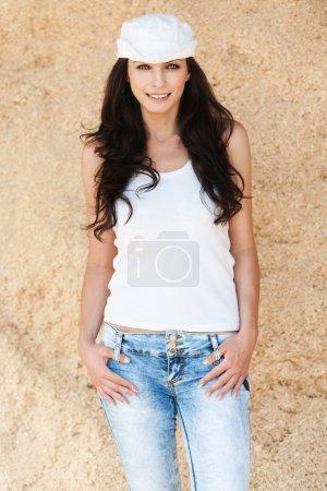 Slender brunette white cap jeans