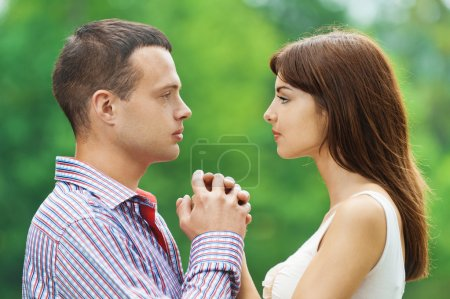Photo for Portrait young couple loving facing each other hold hands background summer green park - Royalty Free Image