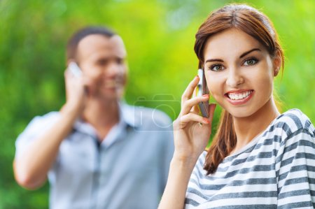 Photo pour Couple heureux jeune belle de portrait homme femme parlant téléphone fond vert parc d'été - image libre de droit