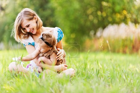Photo for Beautiful young mother and daughter relaxing on grass background summer meadow green grass trees - Royalty Free Image