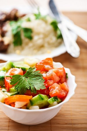 Photo for Close-up summer salad of tomatoes, cucumbers, onions, decorated with sprig of parsley in white bowl, deep in background meat dish with vegetables in white bowl - Royalty Free Image