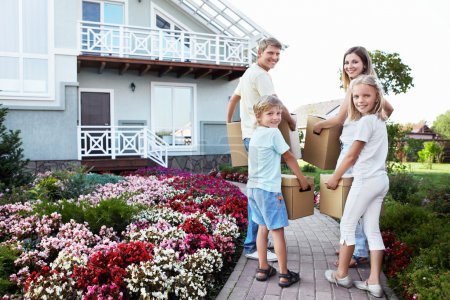 Photo for Family with boxes going to the house - Royalty Free Image