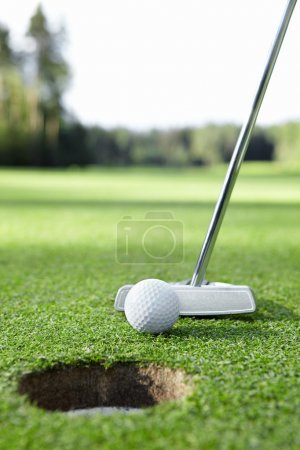 Photo pour Balle et club de golf dans le trou - image libre de droit
