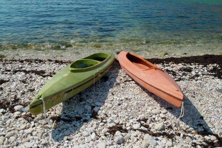 Two colour kayaks on the beach.