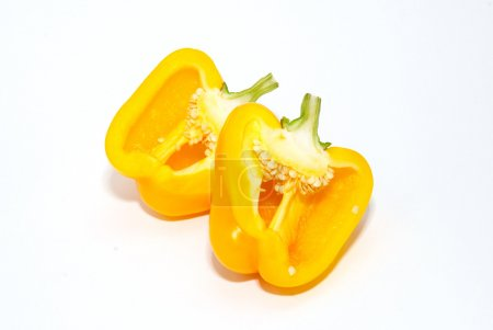 Two halves of slitting yellow paprika isolated on white.