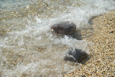 Rocks in the waves and sea foam.