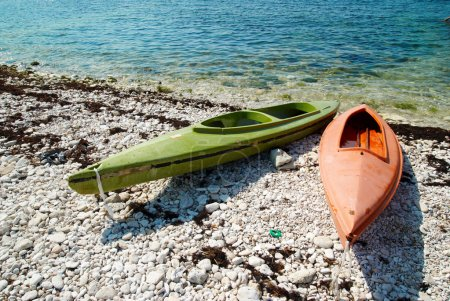 Two colour kayaks on the beach.