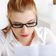 Closeup on young pretty woman in glasses reading f...