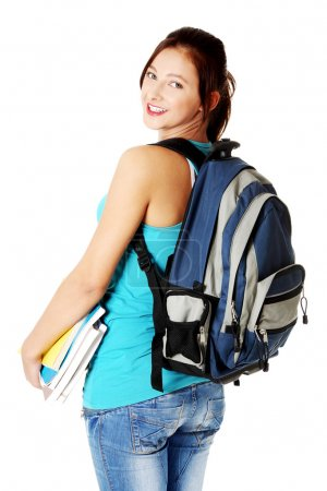 Photo for Young beautiful caucasian teen student with notes smiling and showing her backpack. Isoalted on white. - Royalty Free Image