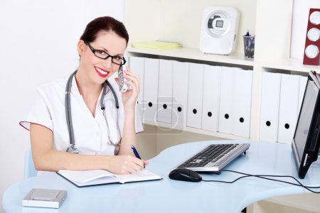Female doctor talking by the phone and writing.