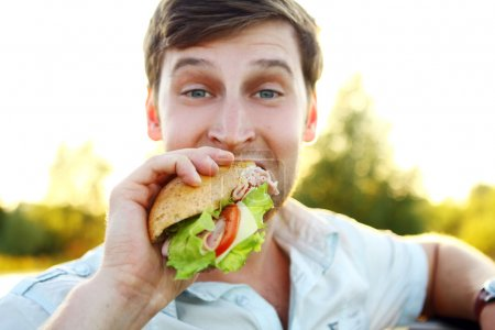 Young man eating sandwich