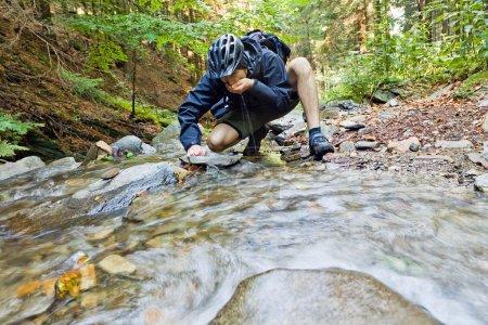 Photo pour Mountain biker l'eau potable provenant d'une source - image libre de droit