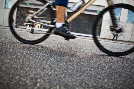 Photo pour Homme en vélo sur la rue de la ville, flou de mouvement et mise au point sélective - image libre de droit