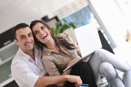 Joyful couple relax and work on laptop computer at modern home
