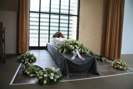 White coffin with sympathy flowers