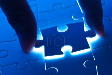 Photo for Pick puzzle piece with mystery back light - Royalty Free Image