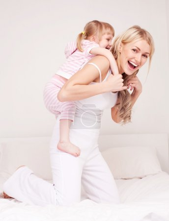 Photo for Happy young mother playing with her daughter on the bed at home - Royalty Free Image