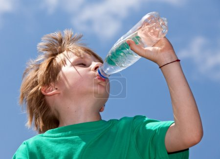 Thirsty boy drinking fresh water outdoors
