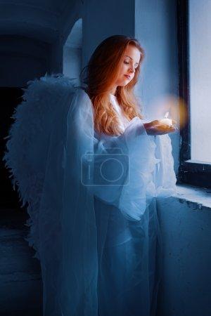 Photo pour Portrait d'un ange avec une bougie debout près de la fenêtre . - image libre de droit