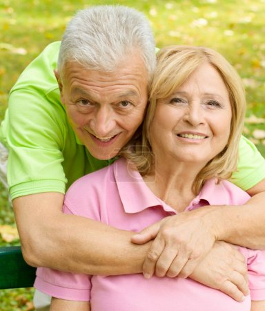 Photo for Portrait of happy senior man embracing senior woman outdoors. - Royalty Free Image