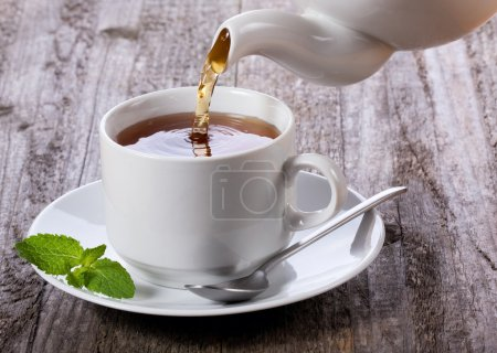 Photo for Pouring tea into cup of tea - Royalty Free Image