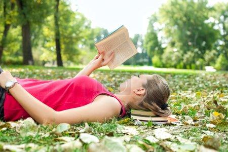 Photo pour Jeune femme relaxant et livre de lecture - image libre de droit