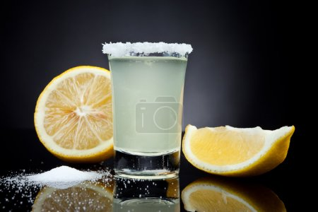 Photo for Shot glass with a lemon on black background - Royalty Free Image
