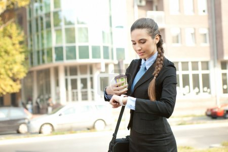 Busy businesswoman checking the time