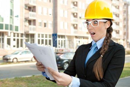 Female engineer reading paperwork , shocked and su...