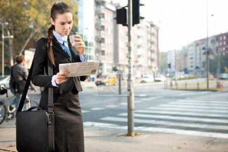 Serious businesswoman reading newspaper
