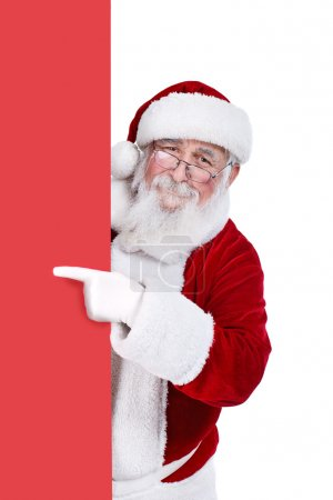 Photo for Santa Claus pointing in blank red banner, isolated on white background - Royalty Free Image