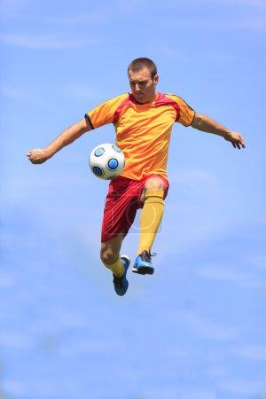 Photo pour Joueur de football donnant un coup de pied au ballon tout en sautant . - image libre de droit