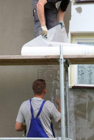 Photo pour Mortier étalant la truelle sur l'isolation en styromousse du mur - image libre de droit