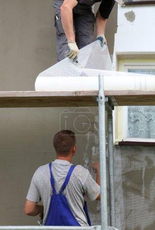 Trowel spreading mortar on styrofoam insulation of...