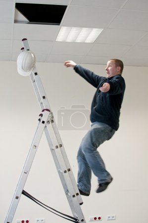 Photo for A young man falls from ladder - Royalty Free Image