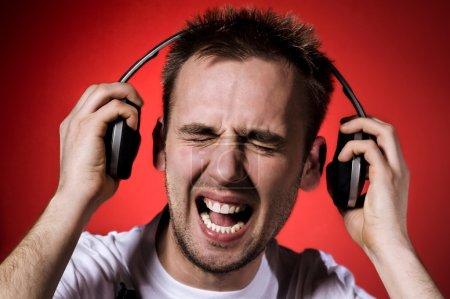 Photo pour Jeune homme avec grimace sur son visage à cause de la musique forte - image libre de droit