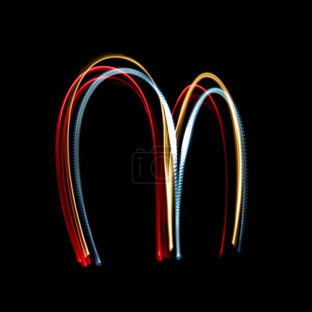 Letter M made from brightly coloured neon lights