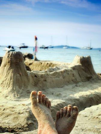 Photo pour Un homme se détend sur la plage après avoir construit un château de sable . - image libre de droit