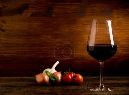 Photo for Photo of delicious red wine goblet with fresh ingredients on wooden table - Royalty Free Image