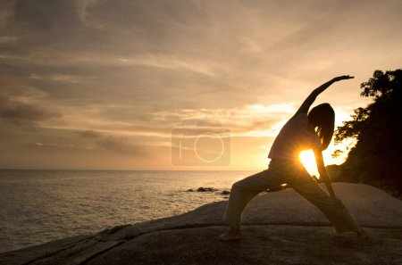 Photo for Asian girl performing yoga on beach, warrior pose - Royalty Free Image