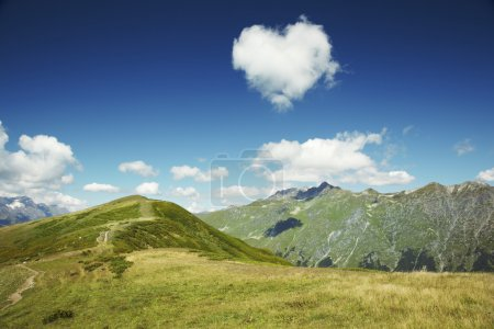 Caucasus mountains.Heart from cloud in the blue sky