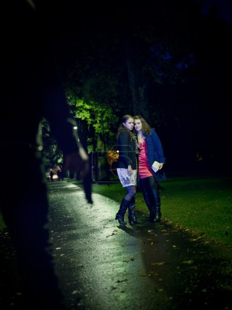 Photo for Man threating two women with a gun at night - Royalty Free Image