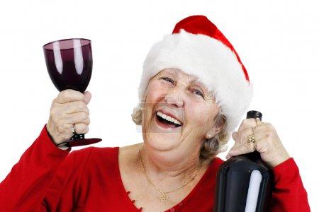 Photo pour Concept de vacances : la femme âgée souriante ou grand-mère porte le chapeau du Père Noël et s'amuse beaucoup à boire à la fête de Noël - image libre de droit